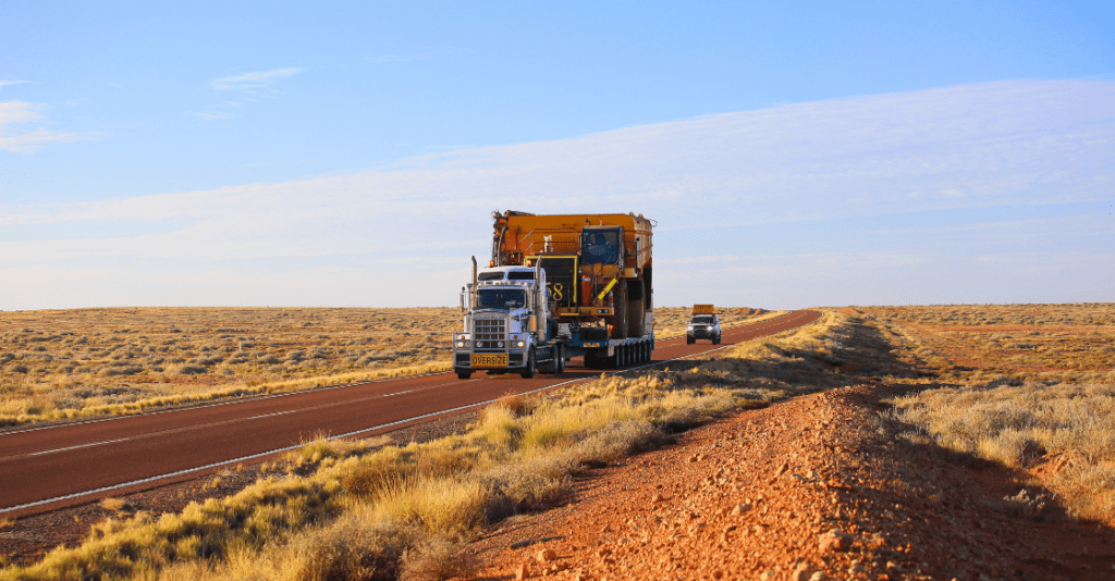A truck transports out of gauge cargo on a desert highway.